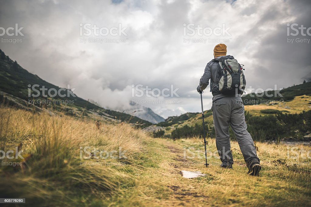 Traveler walking alone in the mountains stock photo