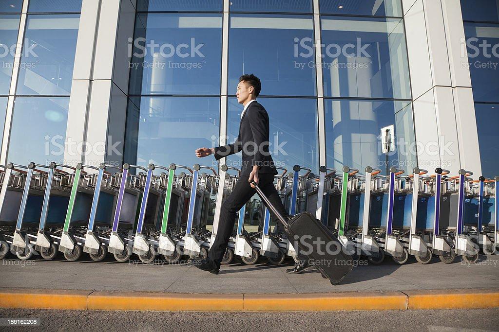 Traveler walking fast next to row of luggage carts royalty-free stock photo