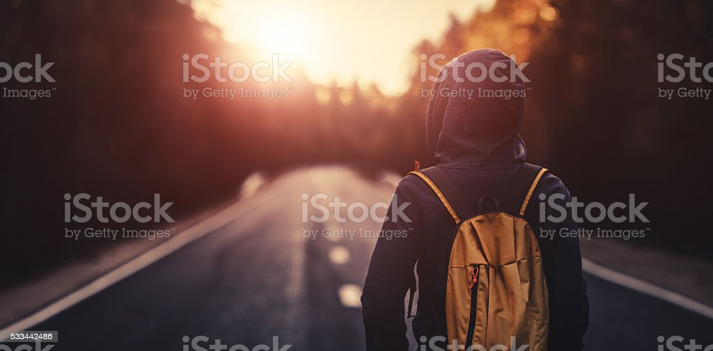 Traveler walking forward alone at sunset stock photo