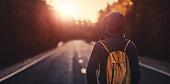 Traveler walking forward alone at sunset