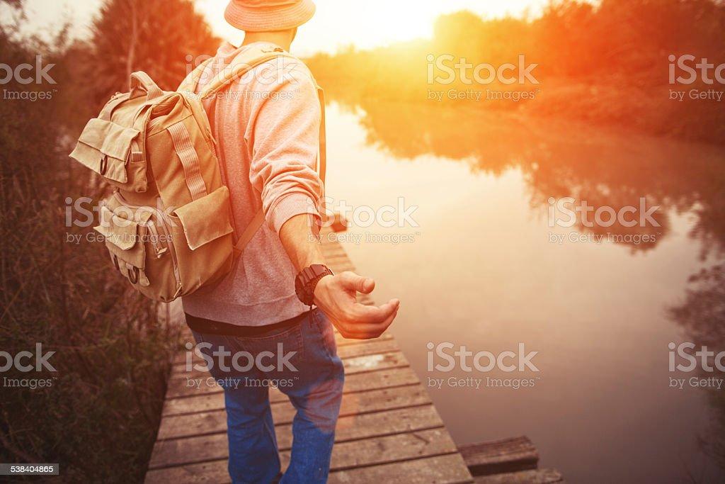 traveler walking over wooden bridge in sunset stock photo
