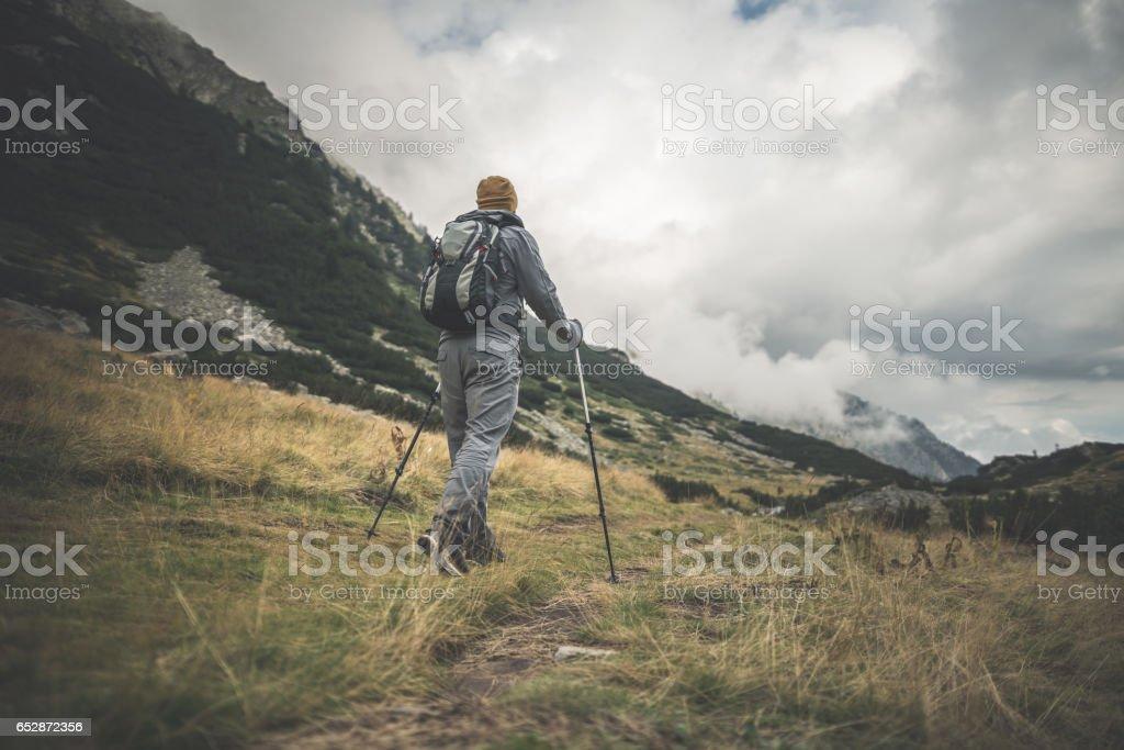 Traveler walks alone in mountains stock photo