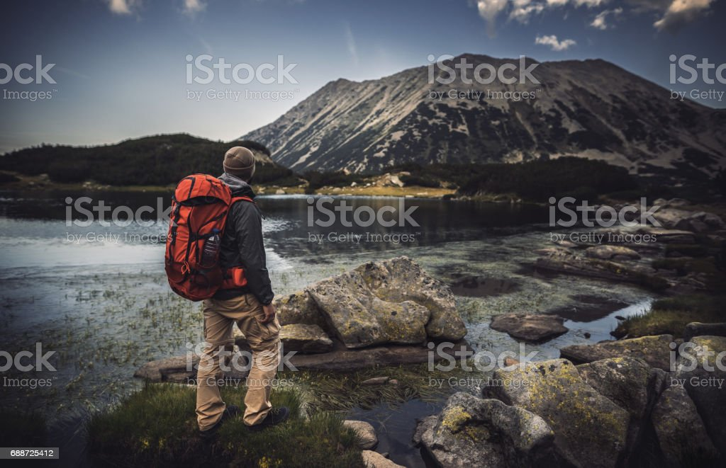Traveler watching the sunset over the mountains stock photo