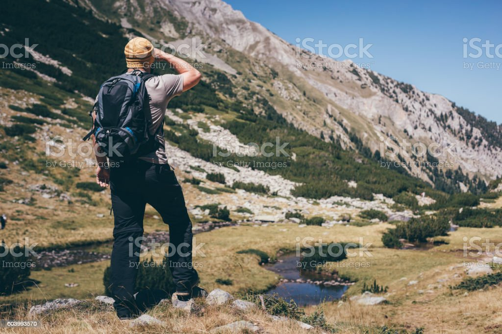 Traveler with a backpack is looking around in mountains stock photo