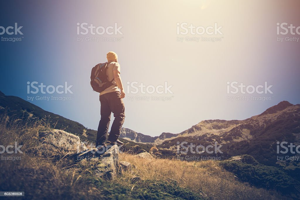 Traveler with backpack in mountains stock photo