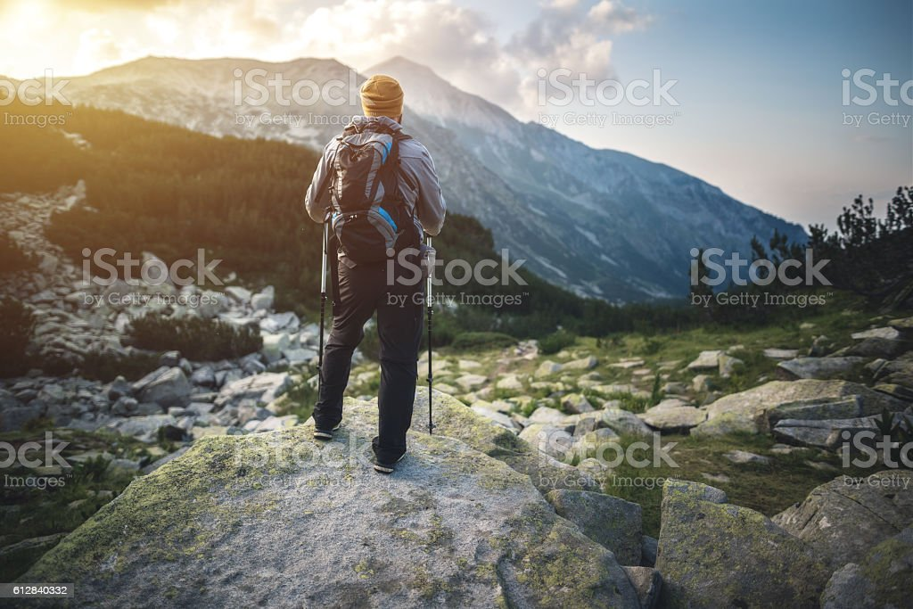 Traveler with backpack looks on a mountain peak on sunset stock photo