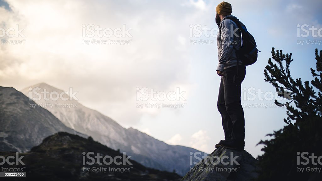 Traveler with backpack looks on a mountain peak stock photo