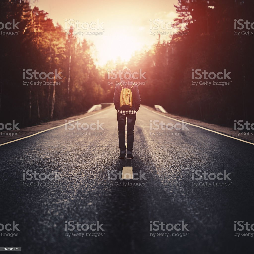 Traveler with backpack walking along the road stock photo