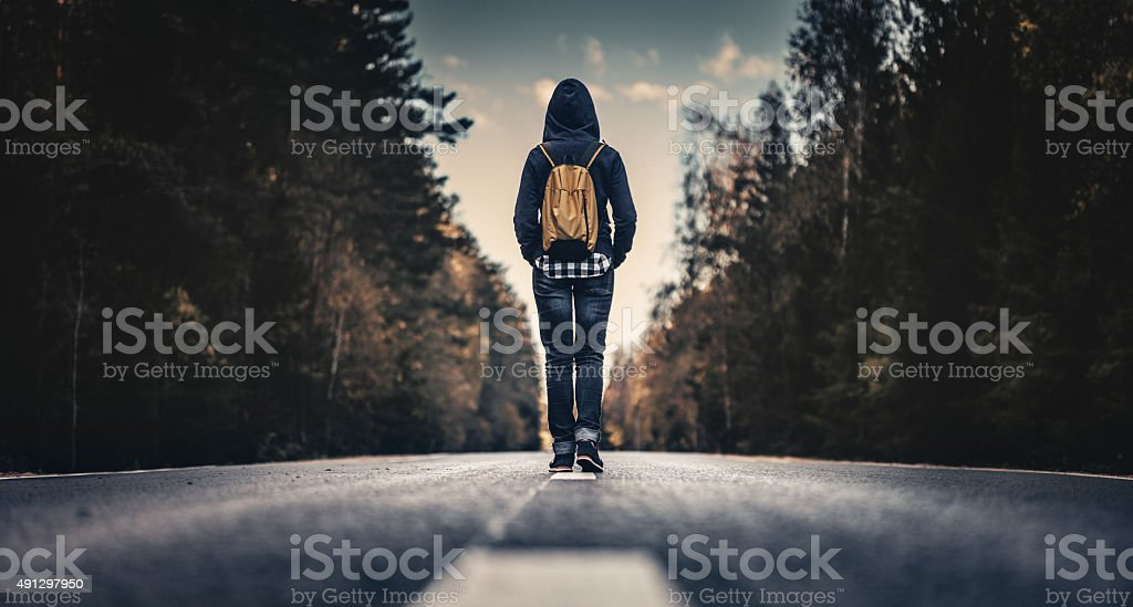 Traveler with backpack walking forward stock photo