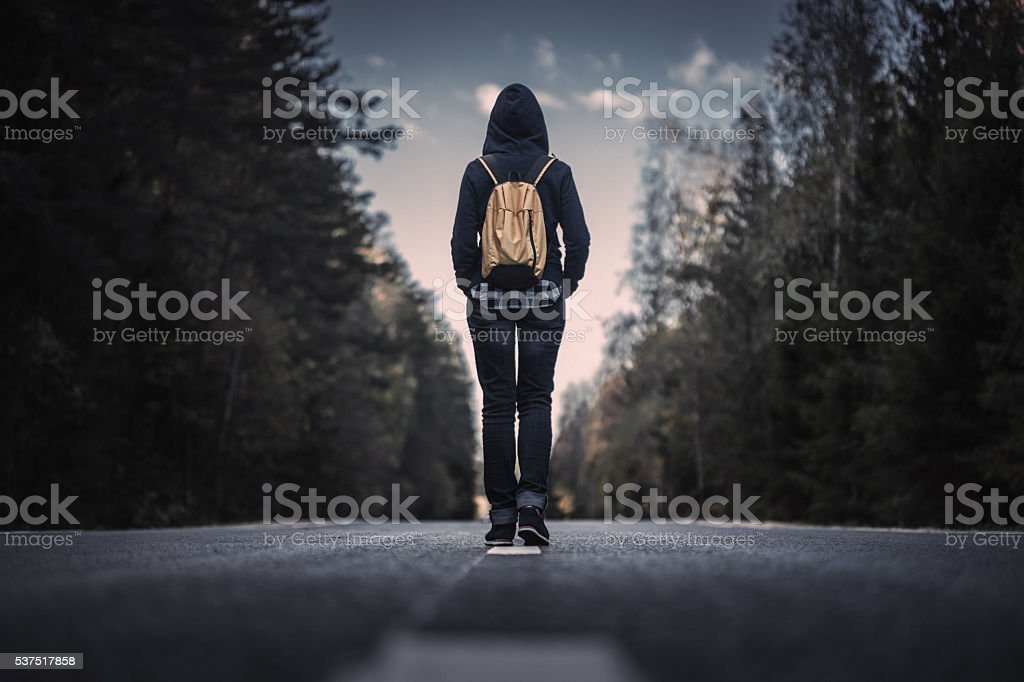 Traveler with backpack walking forward stock photo