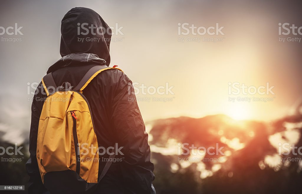 Traveler with backpack walking in mountains at sunset stock photo