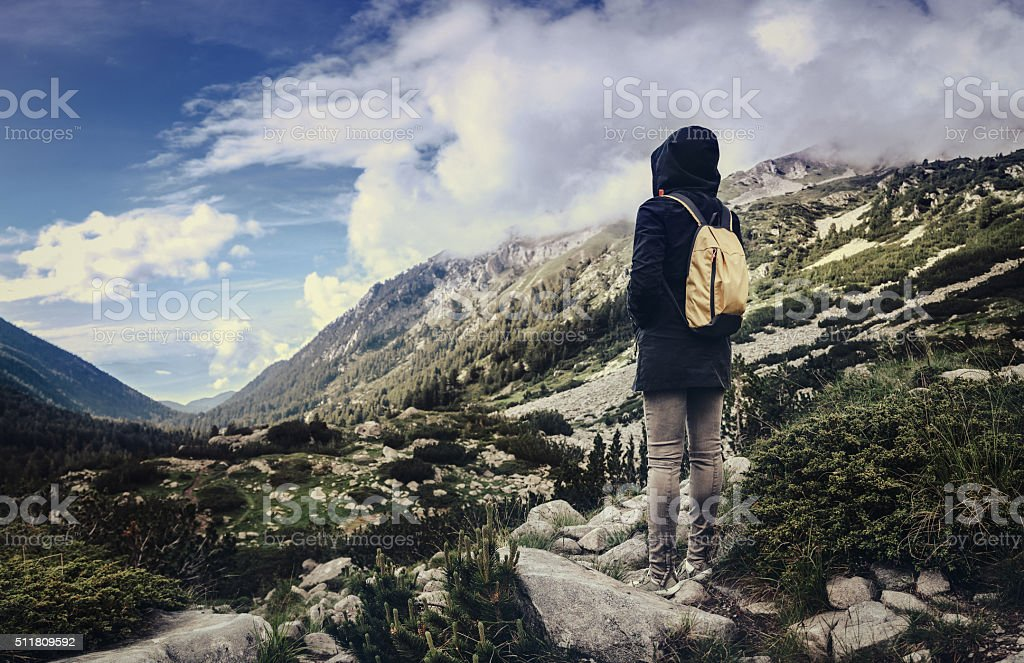 Traveler with backpack walking in mountains stock photo