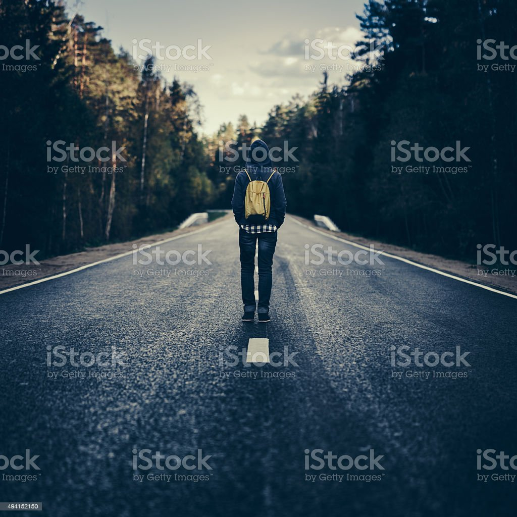 Traveler with backpack walking on the road stock photo
