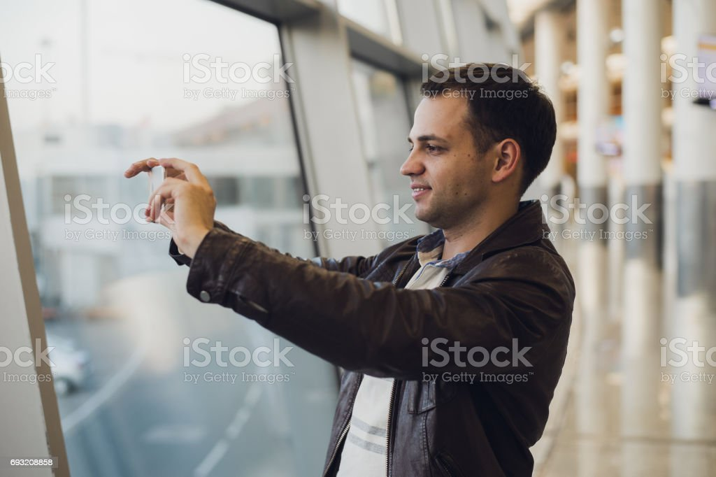 traveler with mobile phone at the airport taking picture of his aircraft. Air Traffic Control facilities at the background stock photo