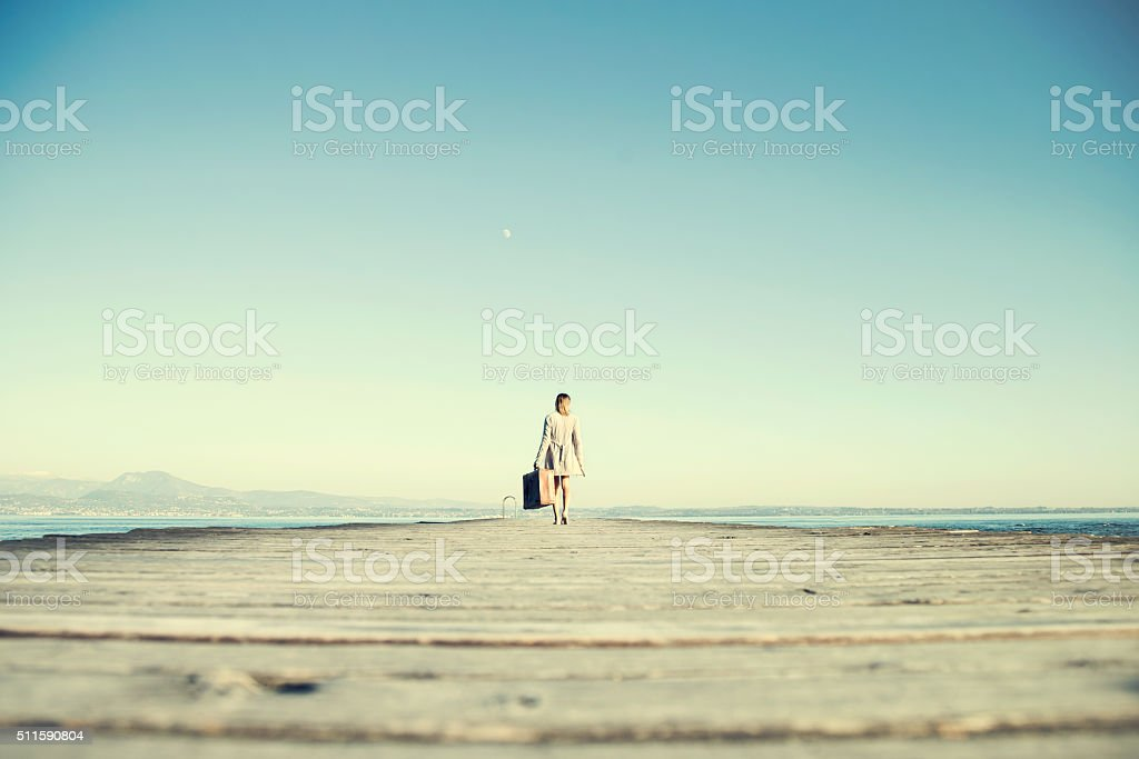 traveler woman cammina to destination with her suitcase stock photo