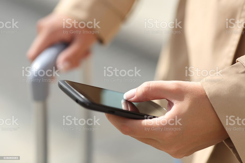 Traveler woman hand consulting a smartphone stock photo