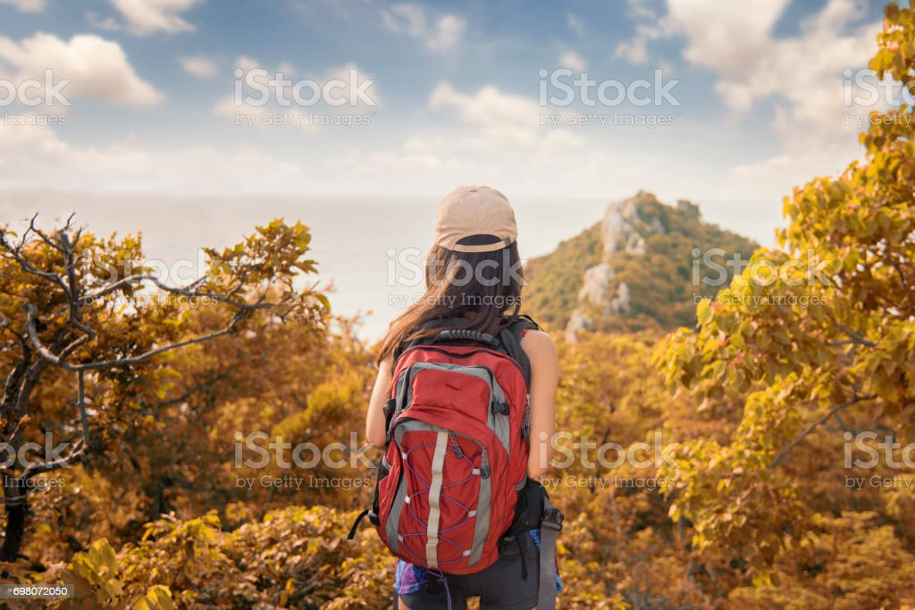 Traveler Woman hiking in mountains with backpack Travel Lifestyle concept adventure summer vacations outdoor mountaineering sport active stock photo