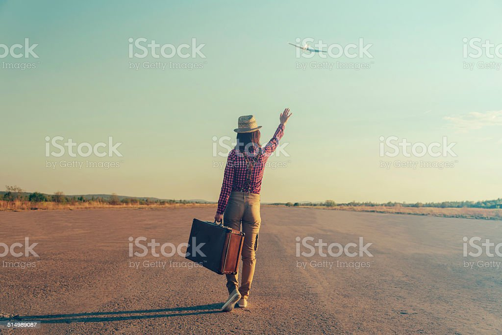 Traveler woman waves her hand to airplane stock photo