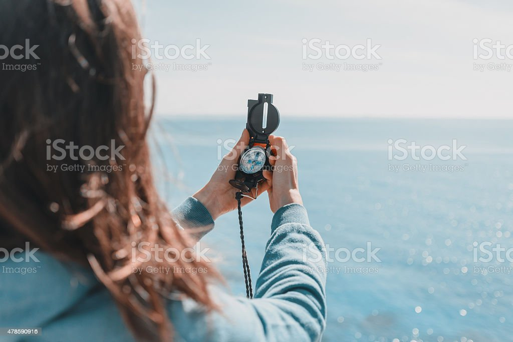 Traveler woman with a compass on coastline stock photo