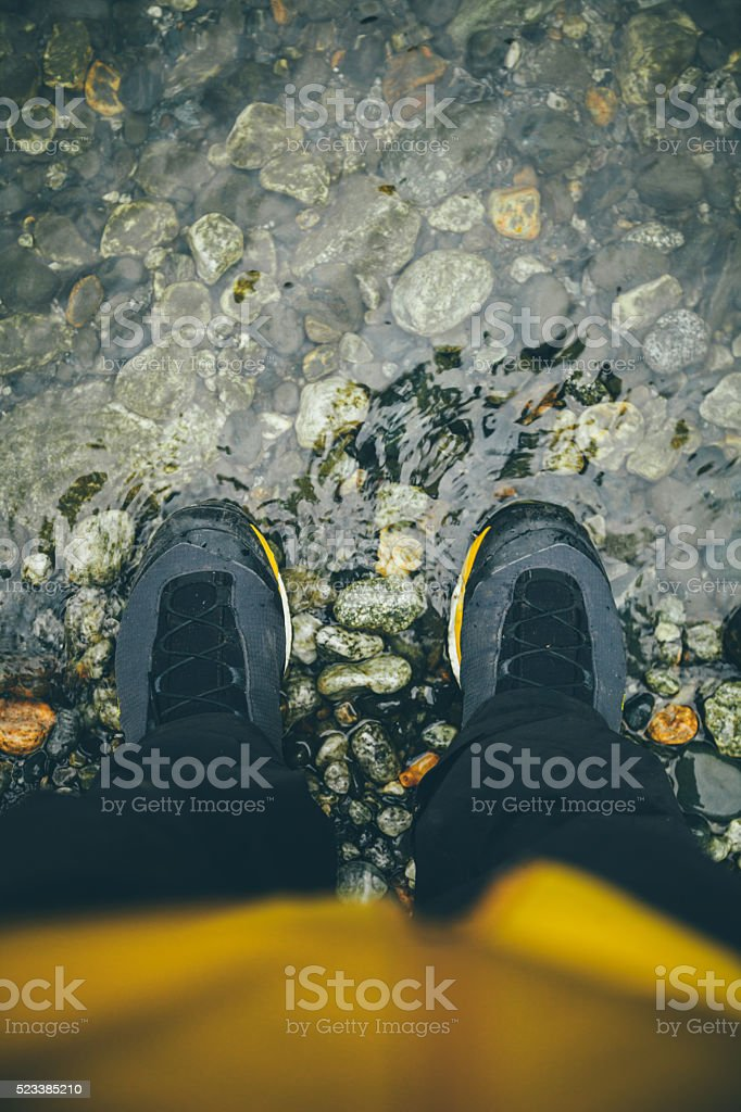 Traveler's body and legs near the water's edge stock photo