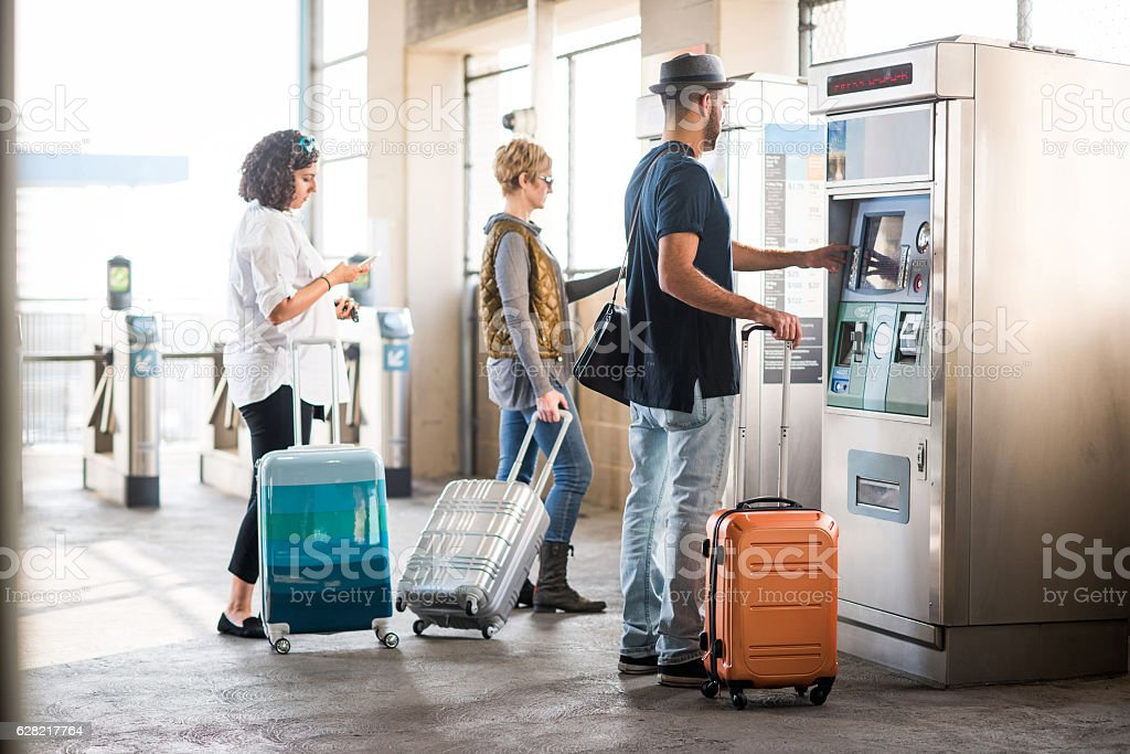Travelers with Suitcases Buying Their Tickets stock photo
