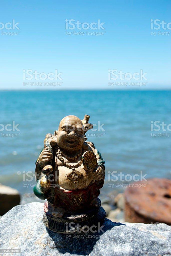 Traveling Buddha on Rocky Shore stock photo