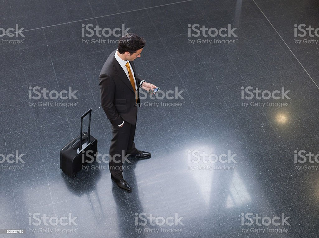 Traveling businessman checking cell phone stock photo
