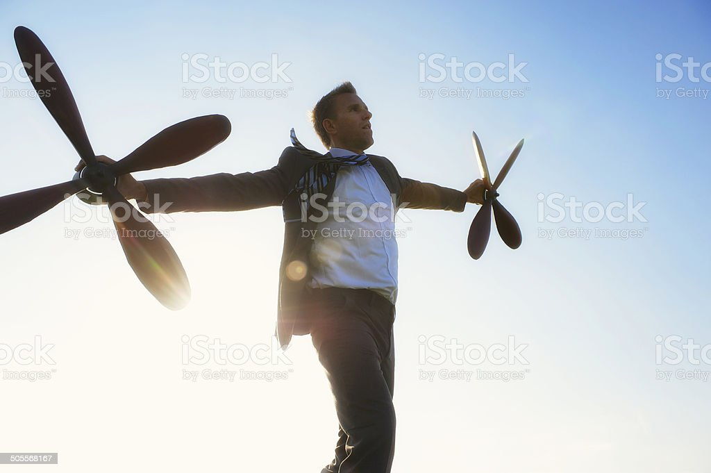 Traveling Businessman Flying with Propellers Against the Sun stock photo