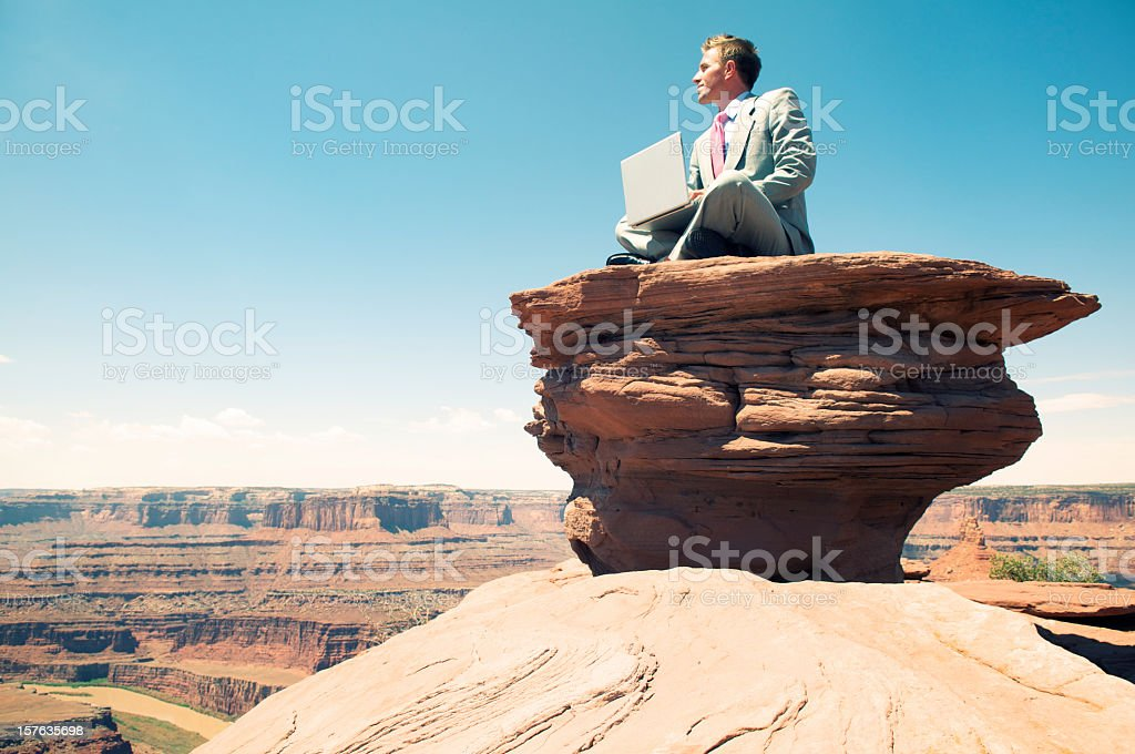 Traveling Businessman Sitting With Laptop on Rock Mesa royalty-free stock photo