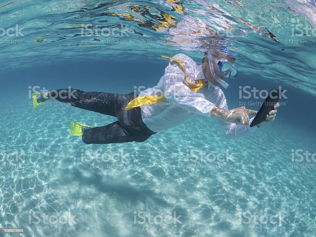 Traveling Businessman Using Digital Tablet Computer Underwater Snorkeling stock photo