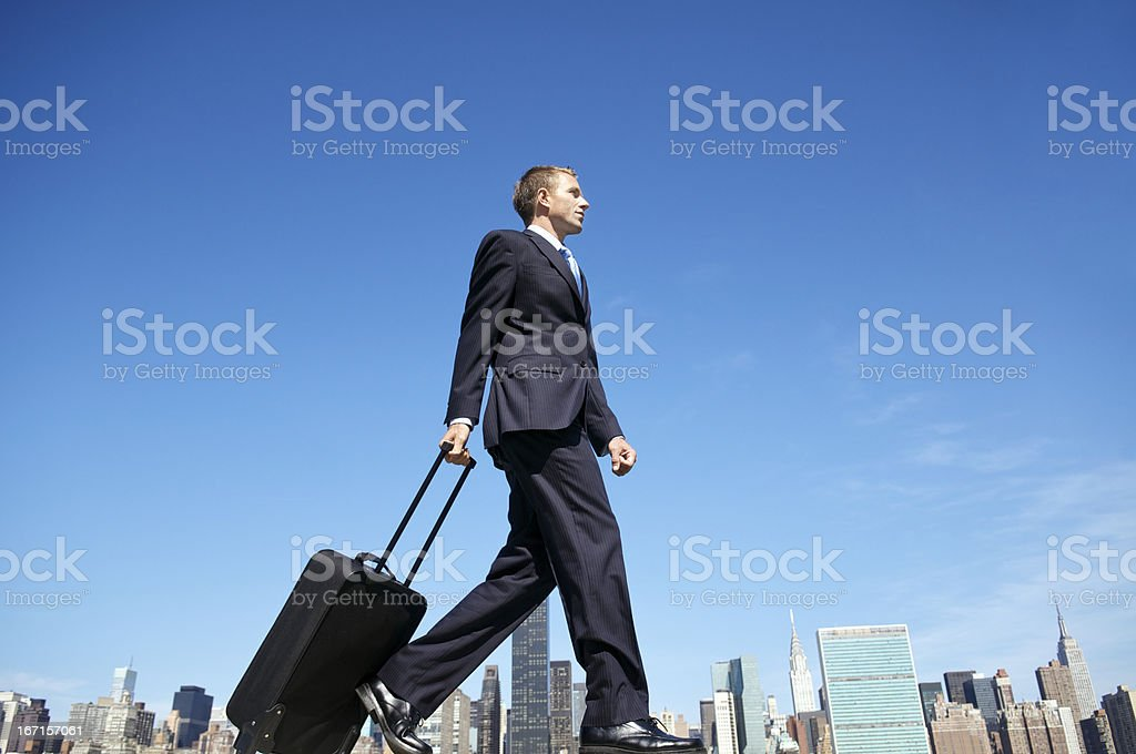 Traveling Businessman Walking with Suitcase Across City Skyline royalty-free stock photo
