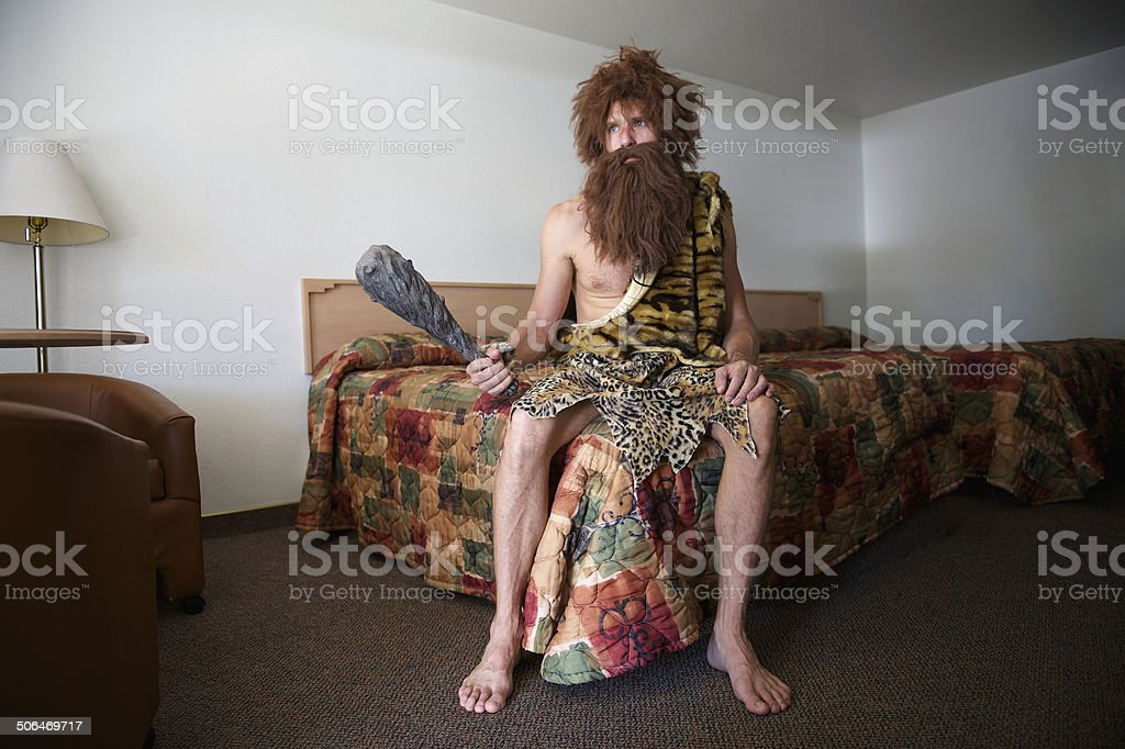 Traveling Caveman Sitting on Old Fashioned Motel Room Bed stock photo