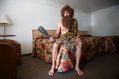 Traveling Caveman Sitting on Old Fashioned Motel Room Bed