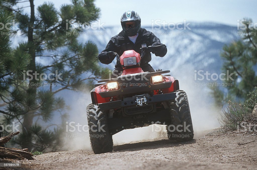 ATV traveling down a dust mountain trail. stock photo