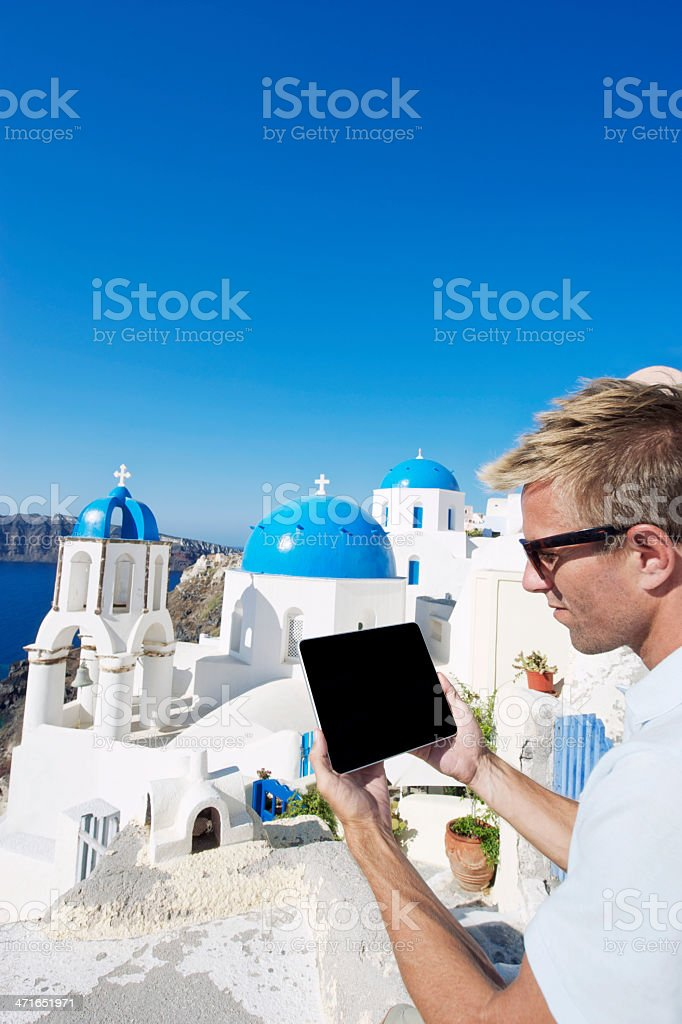 Traveling Man Holds Blank Digital Tablet Computer Santorini Greece Overlook royalty-free stock photo