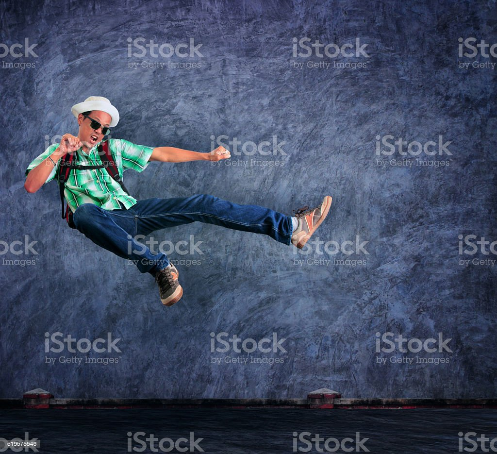 traveling man jumping mid air with exciting emotion stock photo