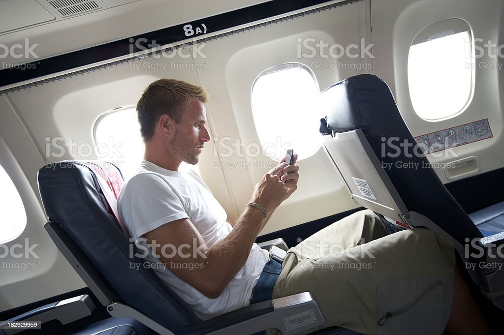 Traveling Man Sitting Texting on Mobile Phone in Airplane Seat royalty-free stock photo