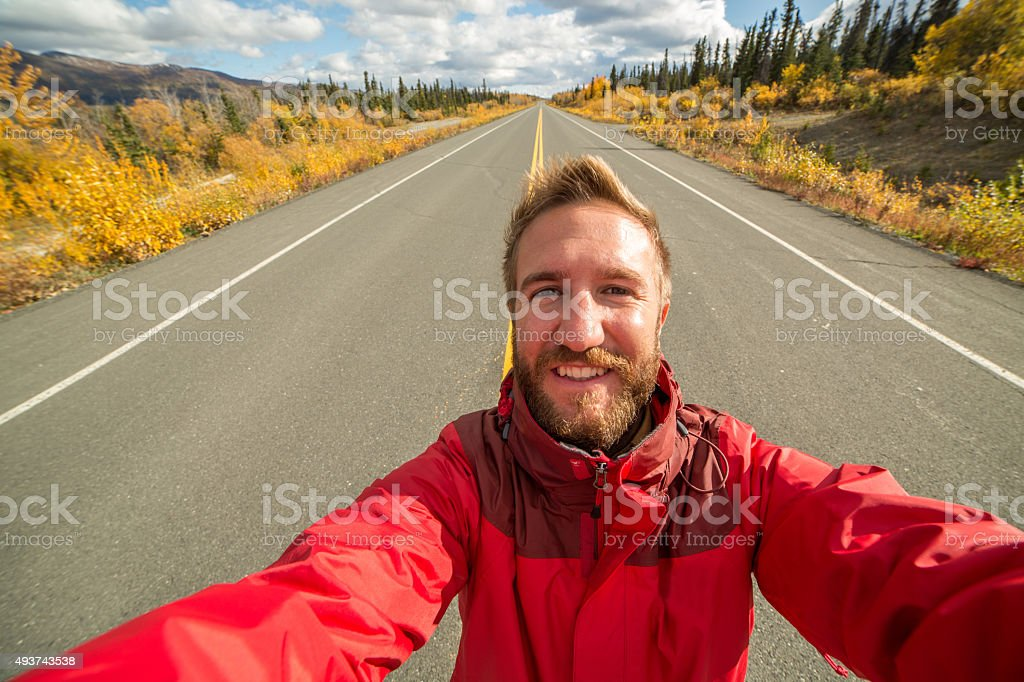 Traveling man takes selfie on empty road stock photo