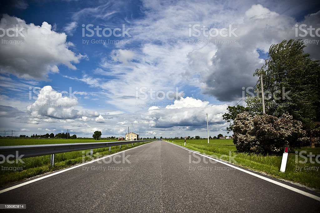 Traveling on a Rural Roadway Dramatic Blue Sky royalty-free stock photo