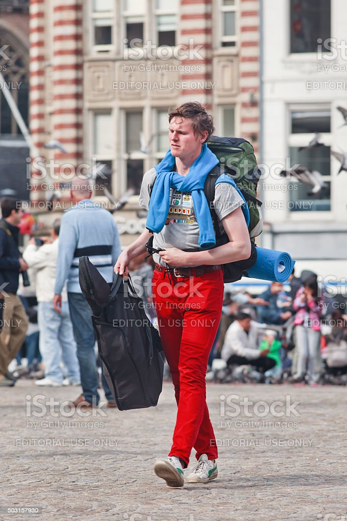 Traveling street performer with guitar bag on Amsterdam Dam Square stock photo