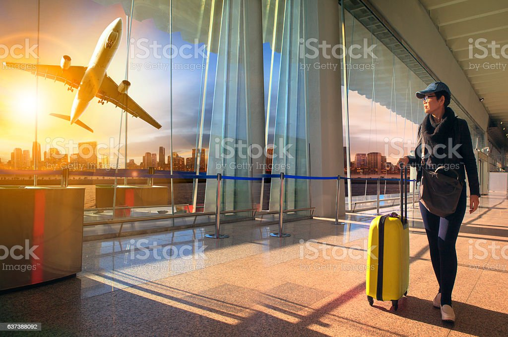 traveling woman and luggage walking in airport terminal and air stock photo