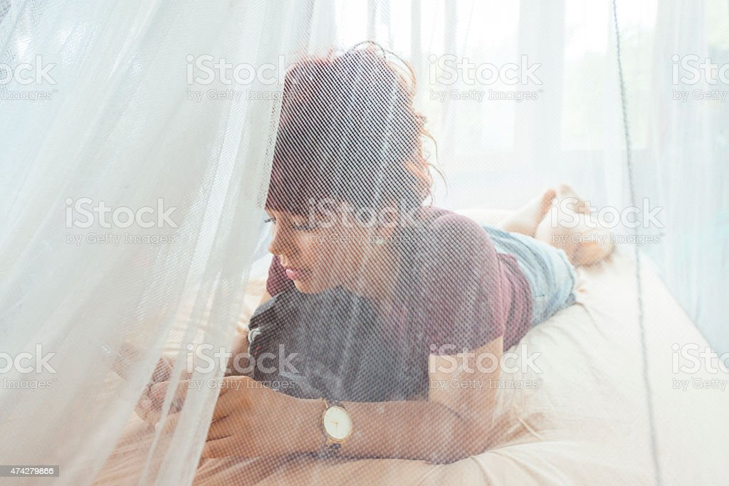 Traveling Woman on Mobile Phone in Bed with Mosquito Netting stock photo
