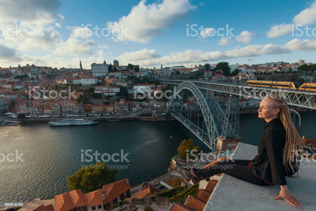 Traveller girl with blonde dreadlocks sitting on the viewpoint opposite Dom Luis I bridge over Douro river, Porto, Portugal. stock photo