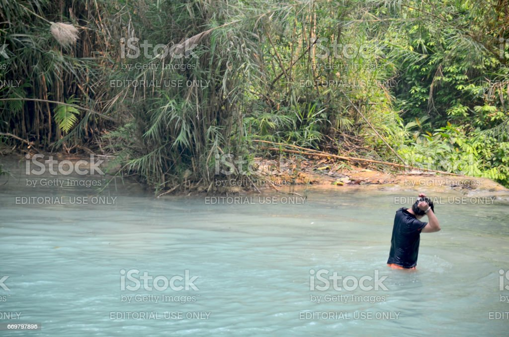 Traveller man play and swimming in pond of Kuang Si Falls stock photo