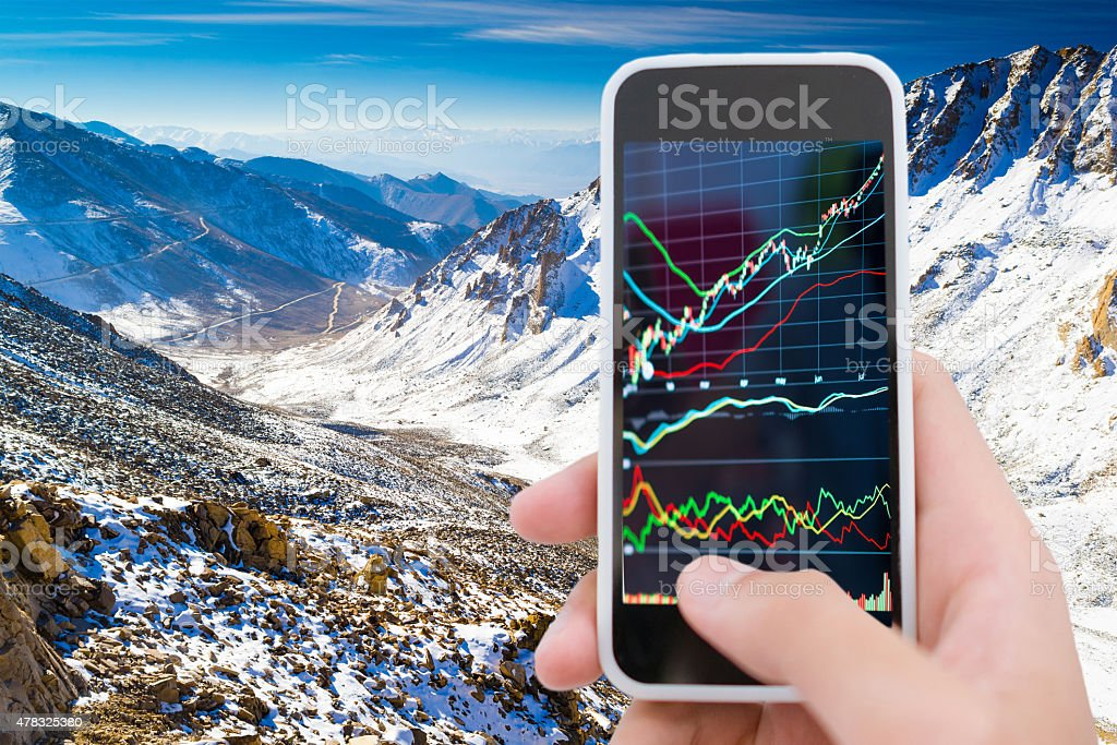 Traveller using smart phone with stockmarket graph stock photo