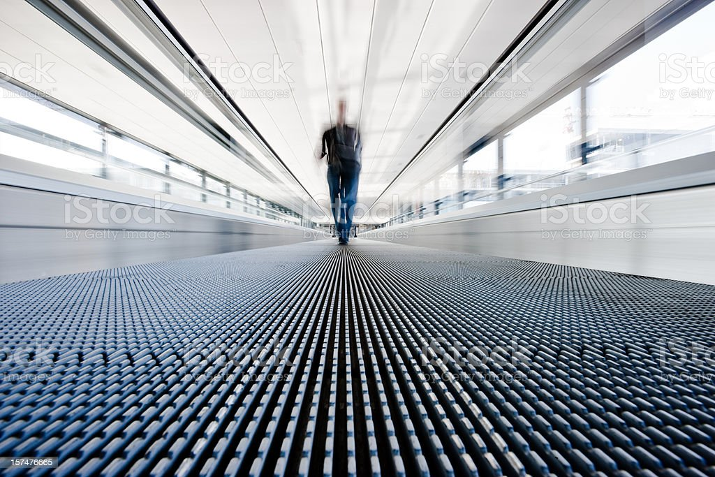 Traveller walking on moving stairway airport walkway royalty-free stock photo