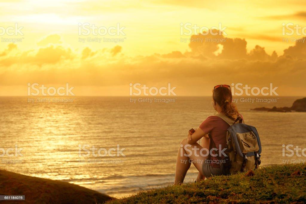 Traveller with backpack enjoying sunset listening to music on peak of mountain. stock photo