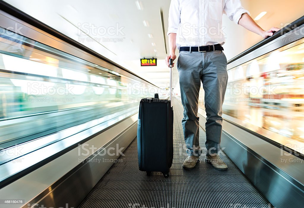 Traveller with black wheeled suitcase on the speedwalk stock photo