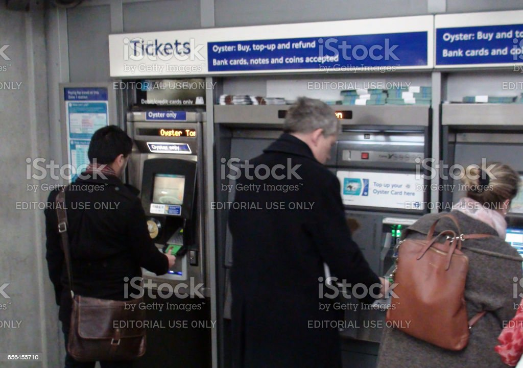Travellers Buying Train Ticket From Self Service Ticket Machine In London England stock photo