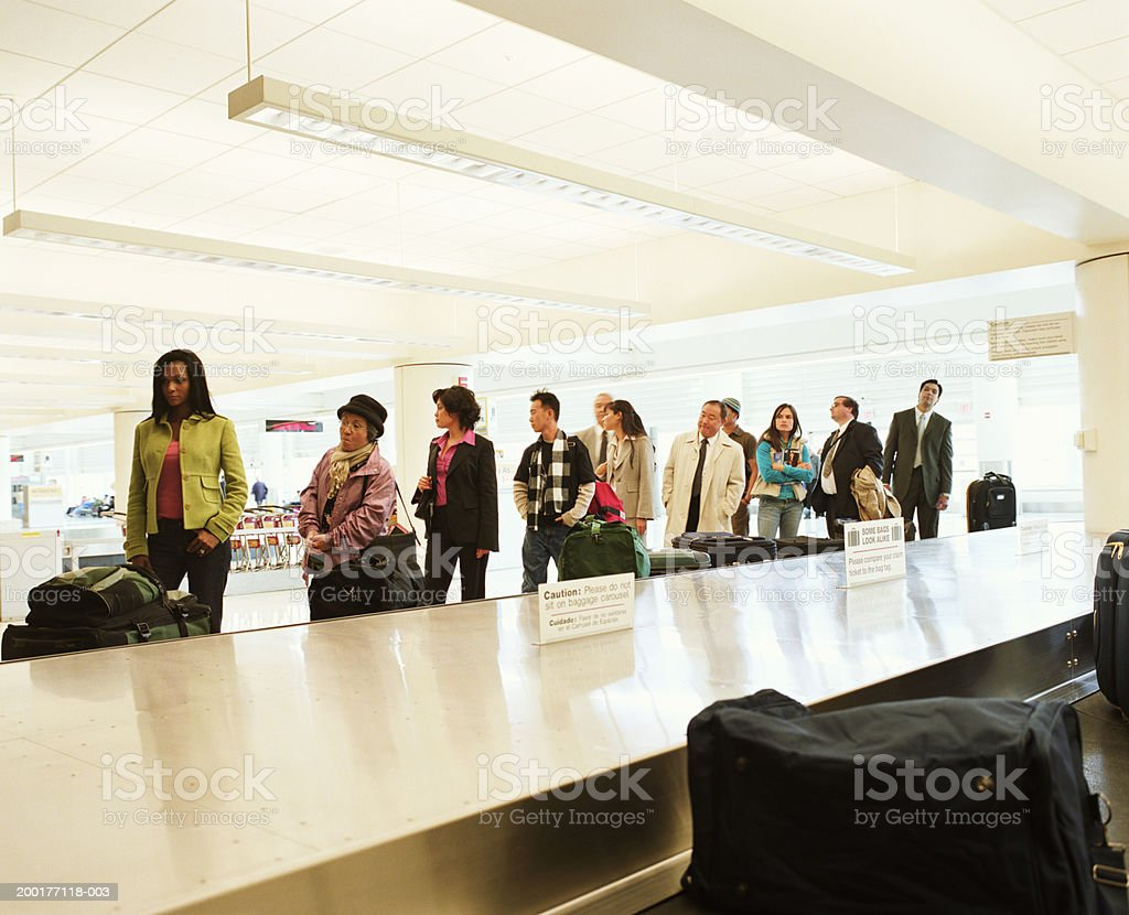 Travellers standing by airport luggage carousel stock photo